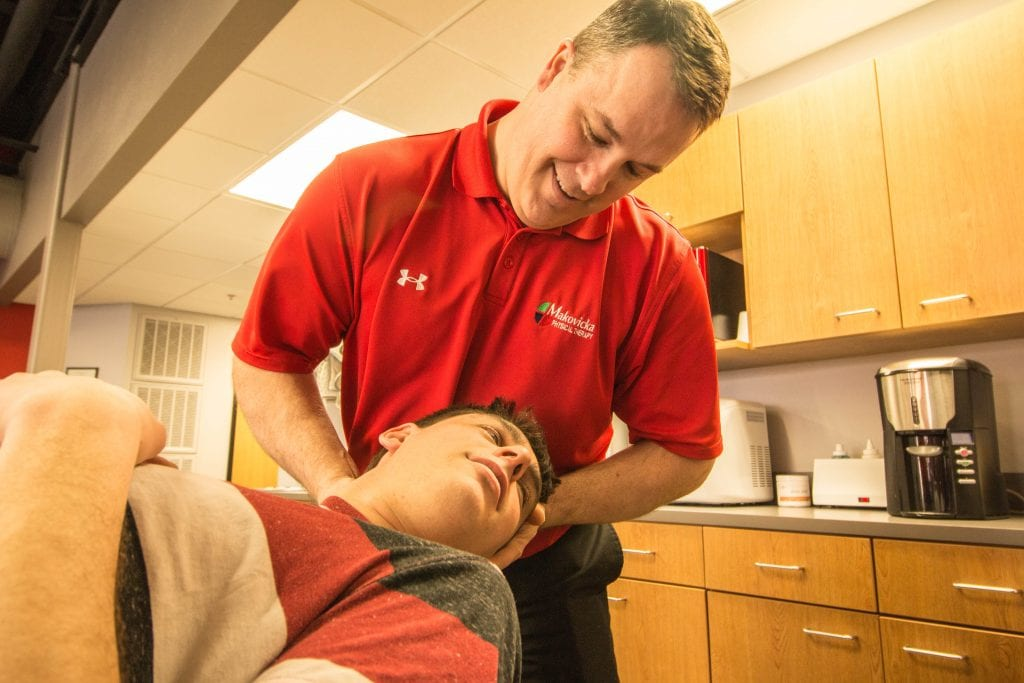 Makovicka phyiscal therapist stretches patient's neck in therapy sesson