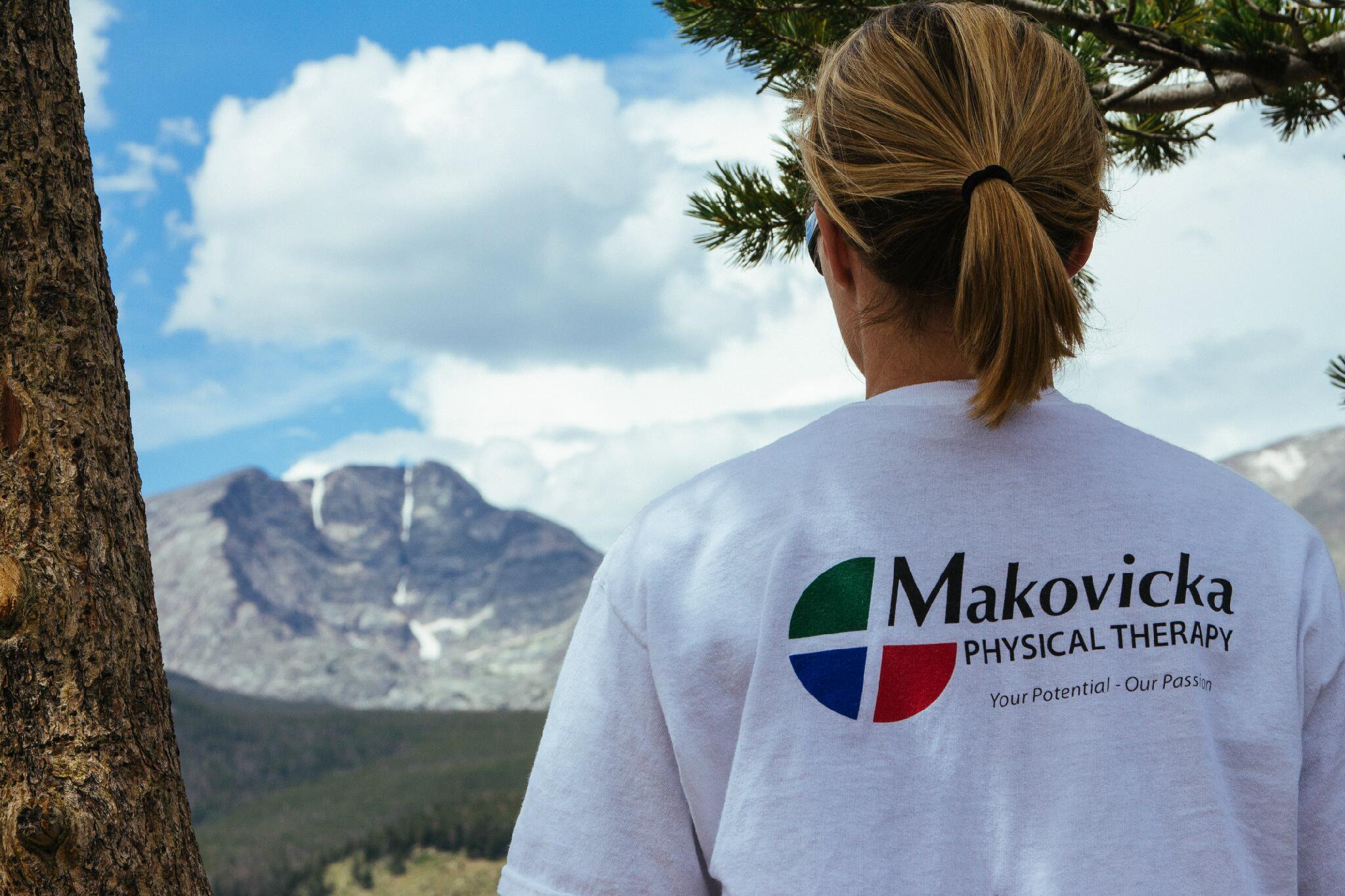 Woman at mountain overlook wearing Makovicka Physical Therapy T-Shirt