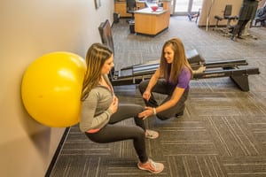 Makovicka physical therapist assists patient in wall sit stability ball exercise